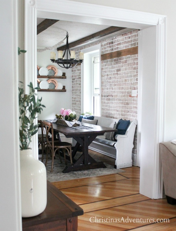 summer farmhouse dining area in a kitchen with brick wall and wood beams