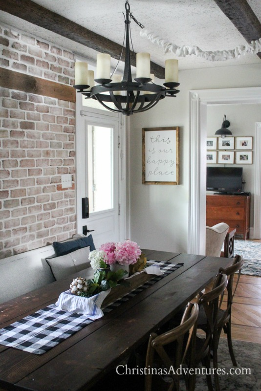 eat in kitchen with brick wall wood beams and wood farmhouse table