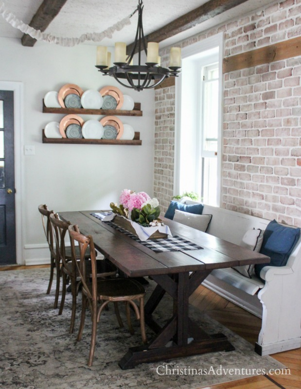 Wood Farmhouse Table With Brick Wall And X Back Chairs