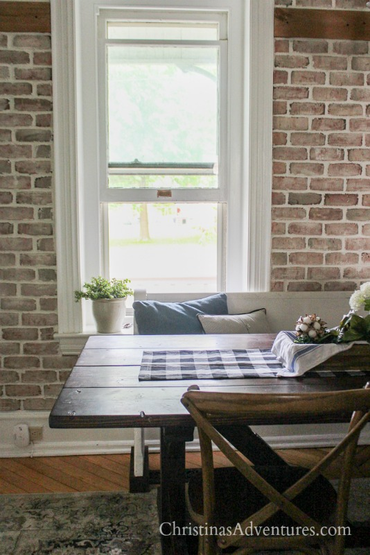 old house fixer upper with brick wall behind the wood farmhouse dining table