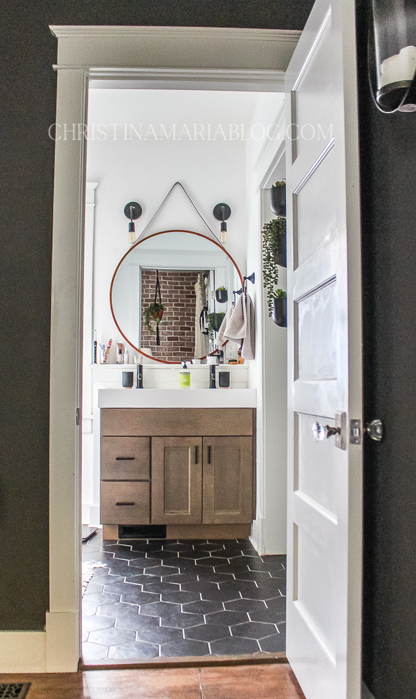 black hex tiles and wood vanity with round mirror