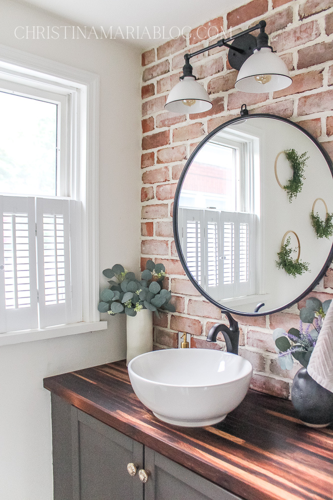 butcher block small bathroom brick wall and round mirror with a vessel sink and black faucet