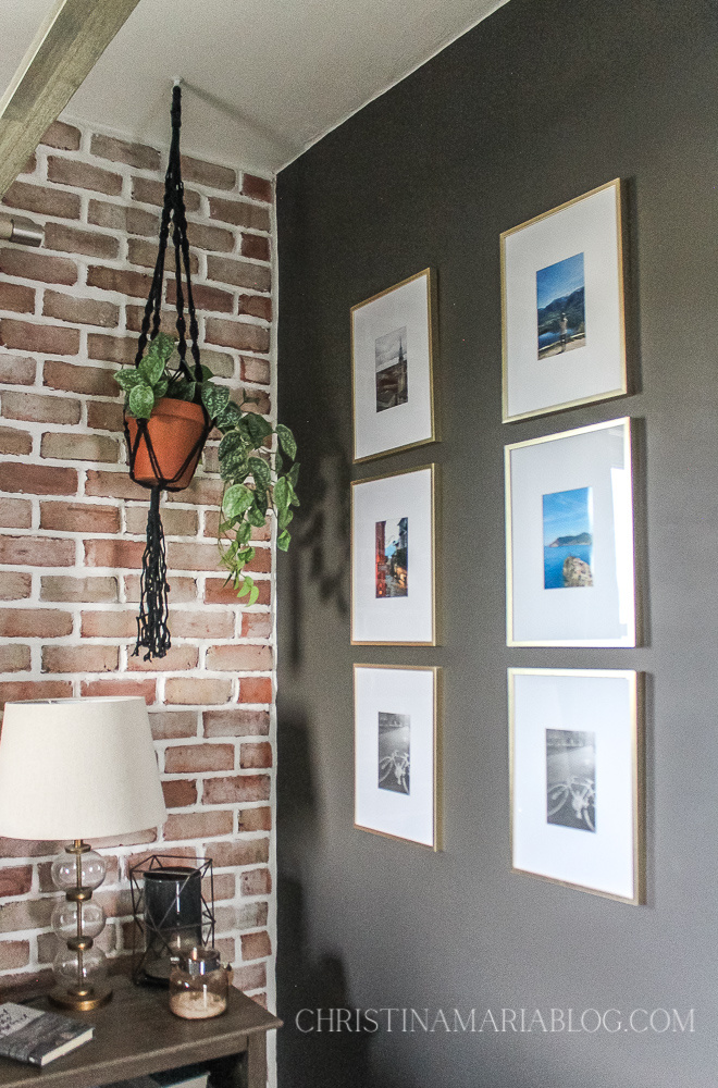 gold frame picture frames on a dark gray wall with brick accent wall and black macrame hanging plant