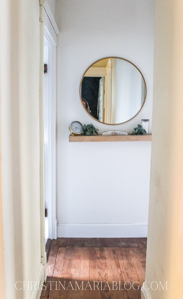end of hallway round mirror with floating shelf