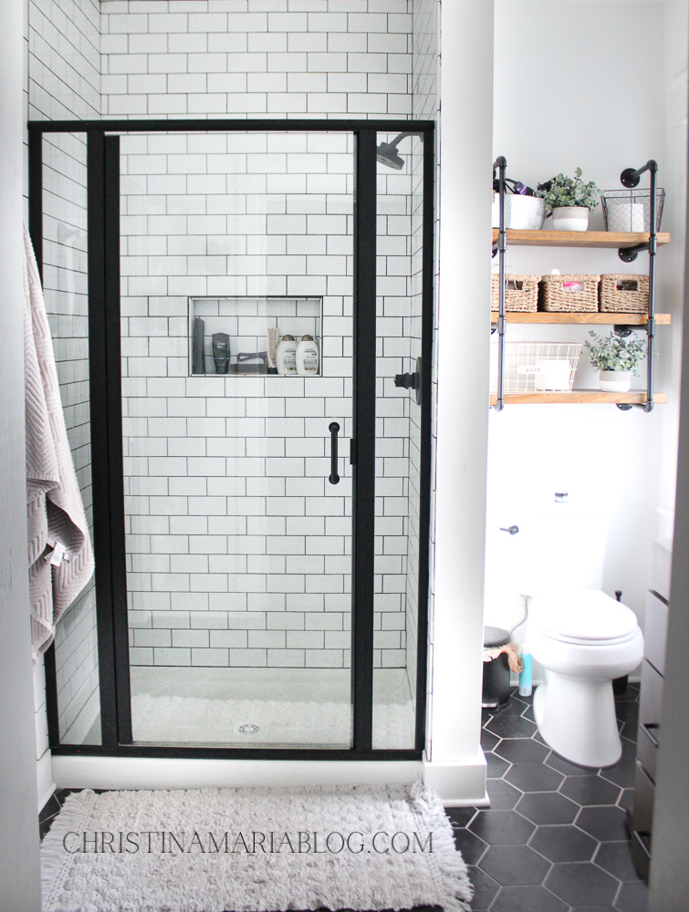 white subway tile shower with black framed glass door