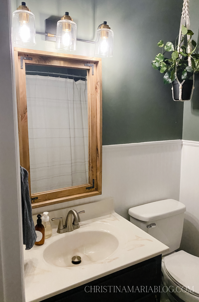 wood framed bathroom mirror and beadboard small bathroom