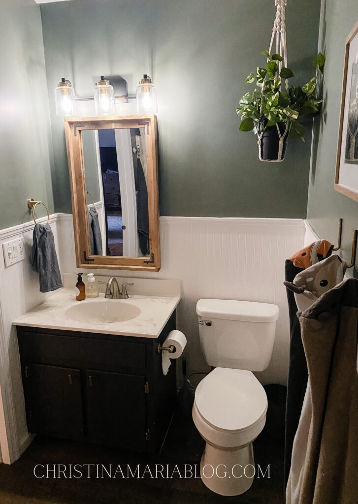 small bathroom makeover green walls white bead board black vanity wood framed mirror