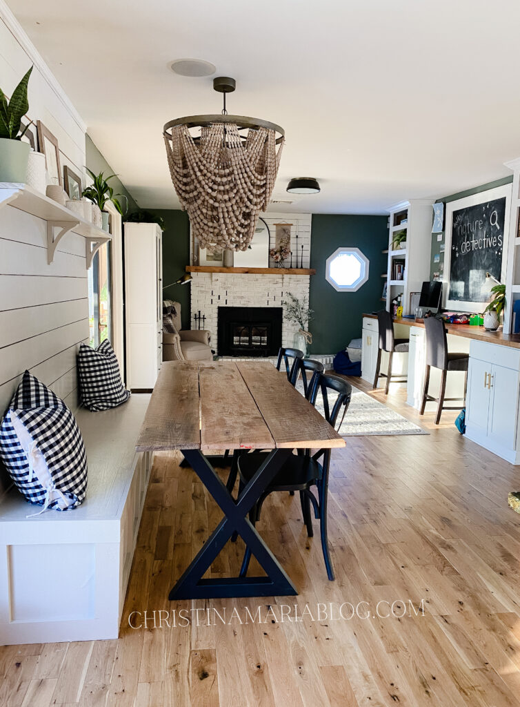 open concept living room white fireplace shiplap home office dining area banquette