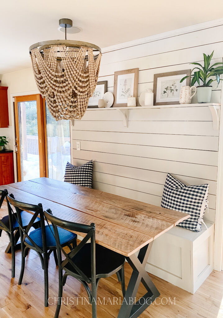wood bead chandelier banquette wood table black chairs