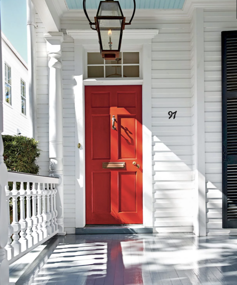 red front door with white exterior and blue porch ceiling black shutters
