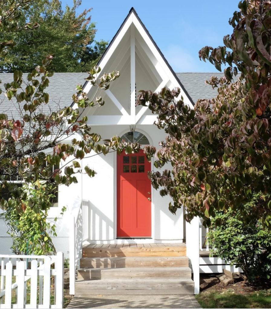 red door on a small white church