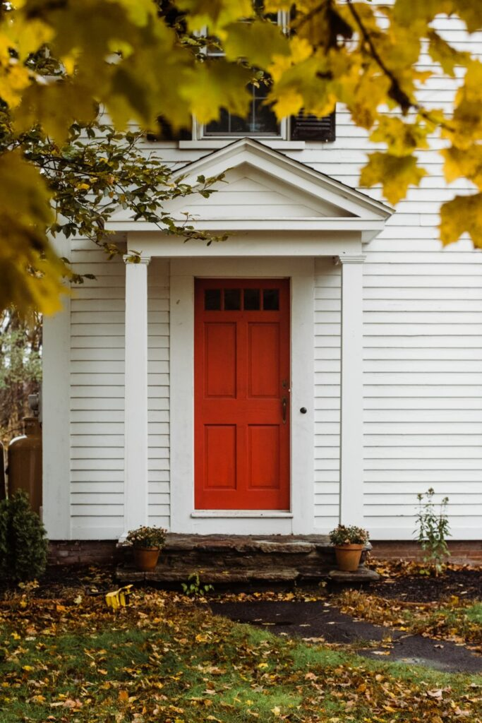 red front door with white siding