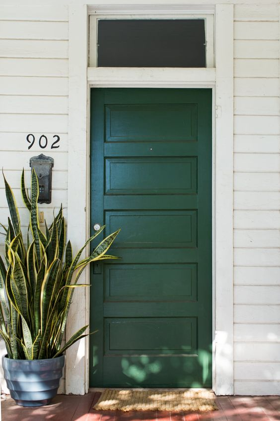 dark green front door with white siding and transom