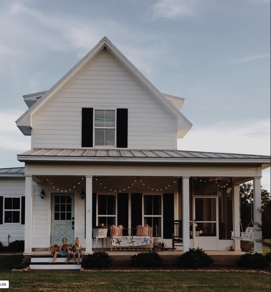 black and white farmhouse with blue front door