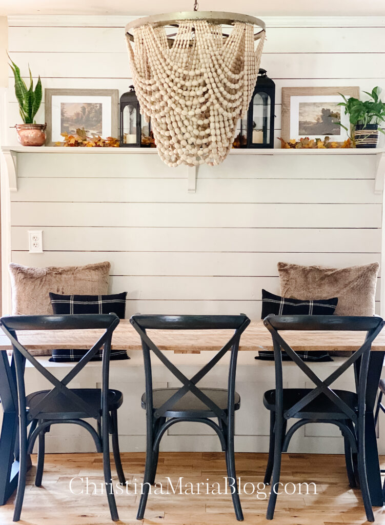 Banquette Fall Decorating with black x back chairs and wood bead chandelier